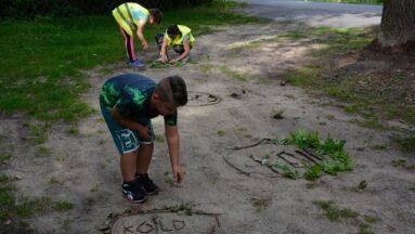 Dzieci układają w plenerze logo KOLD z szyszek, patyków itp.