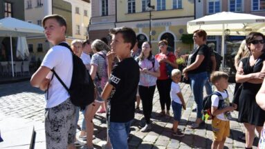 Uczestnicy stoją na rynku w Poznaniu