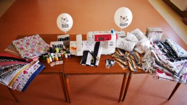 """Stół, na którym poukładane są materiały do szycia oraz balony z logiem """"Działaj Lokalnie"""""""