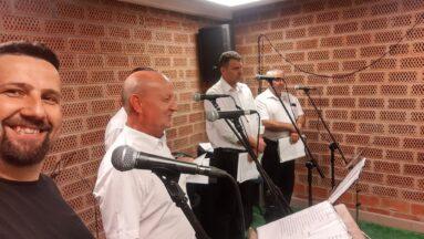 Grupa mężczyzn stoi przy mikrofonach w studiu nagraniowym