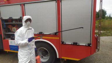 Osoba ubrana w kostium ochronny stoi przy samochodzie