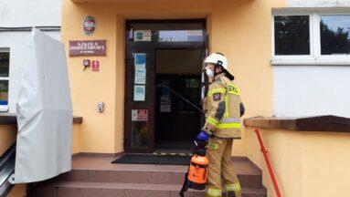 Osoby odkażają wejście do szkoły