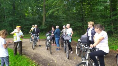Na zdjęciu widzimy grupę osób biorącą udział w rajdzie rowerowym