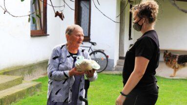 Osoba daje chleb seniorce