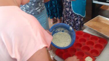 Kobieta wypełnia foremkę na babeczki ciastem