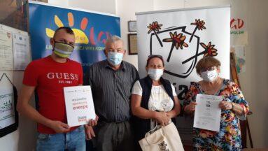 Grupa grantobiorców pozuje do zdjęcia pokazując podpisane umowy