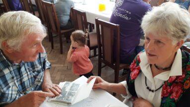 Dwie starsza osoby rozmawiają przy stole
