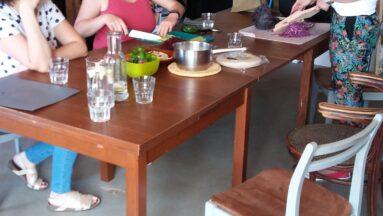 Na zdjęciu widać grupę osób przy stole