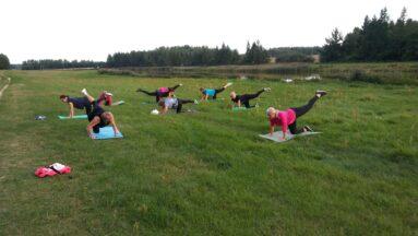 Grupa kobiet ćwiczących w plenerze