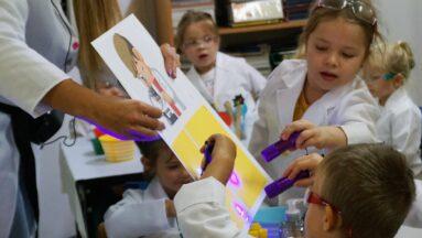 Grupa dzieci przeprowadza eksperyment pod okiem opiekunki