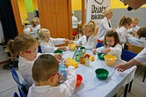 Grupa dzieci siedzi przystoliku wjadalni zamienionej wtymczasowe laboratorium