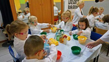 Grupa dzieci siedzi przy stoliku w jadalni zamienionej w tymczasowe laboratorium