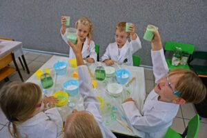 Grupa dzieci ubrana wkitle podnosi kubki zgotowym mydłem