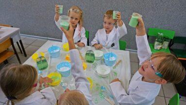 Grupa dzieci ubrana w kitle podnosi kubki z gotowym mydłem