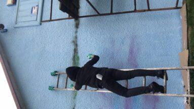 Osoba stoi na drabinie i maluje mural.