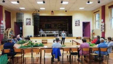 Grupa osób w sali podczas prelekcji