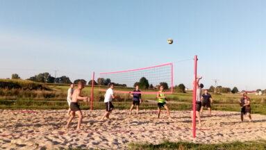 Na zdjęciu widzimy grupę osób grających w siatkówkę plażową