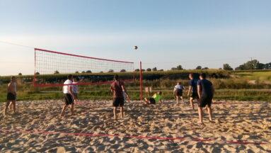 Na zdjęciu widać grupę osób grającą w siatkówkę