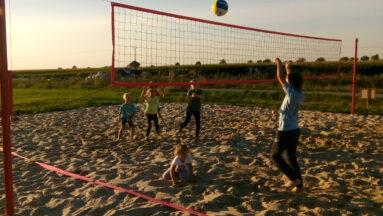 Na zdjęciu widać dzieci grające w siatkówkę plażową
