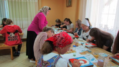 Grupa dzieci tworzy ikony podczas warsztatów