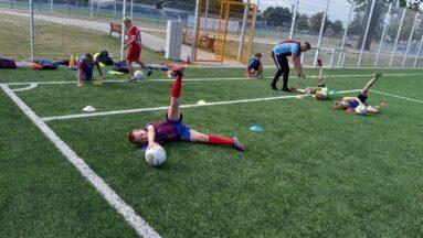 Grupa dzieci ćwiczy na boisku