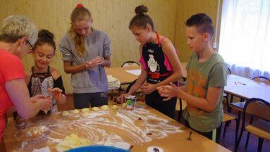 Dzieci i seniorki formują ciasto