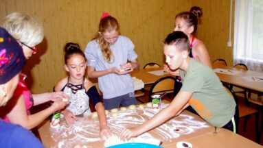 Grupa dzieci i seniorek formuje ciasto na pączki