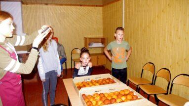Grupa dzieci i seniorek stoi przy stołach zastawionych kartonami z gotowymi pączkami