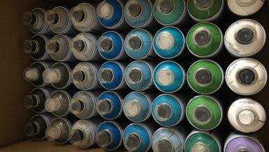 Zdjęcie przedstawia puszki z farbą w sprayu w różnych kolorach.