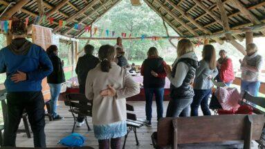 Grupa osób stoi pod wiatą i słucha prelegentki