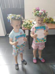 Dzieci zwiankami nagłowie pozują dozdjęcia, pokazując swoje dyplomy