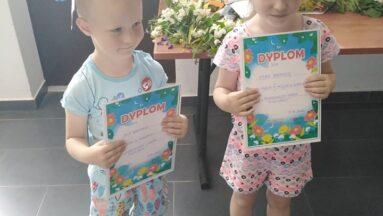 Dzieci z wiankami na głowie pozują do zdjęcia, pokazując swoje dyplomy