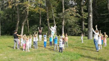 Zając kicak z dziećmi ćwiczą na tle lasu