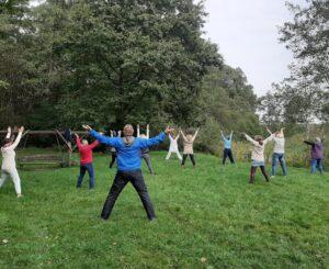 Grupa osób ćwiczy qigong wplenerze