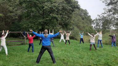 Grupa osób ćwiczy qigong w plenerze