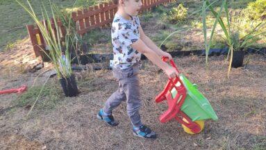 Na zdjęciu widać małego chłopczyka pomagającego w pracach ogrodniczych