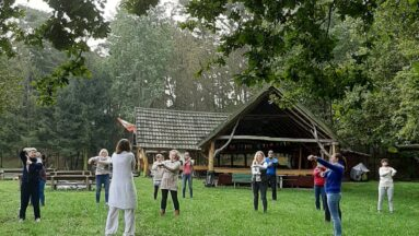 Grupa osób wspólnie ćwiczy na polanie