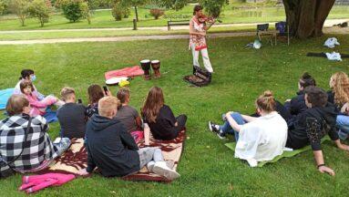 Grupa osób słucha prelekcji w plenerze