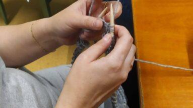 Zbliżenie na dłonie osoby robiącej na drutach