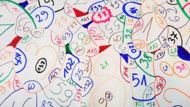 Na zdjęciu widać liczby wypisane kolorowymi markerami na kartce