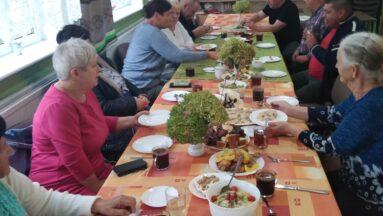 Osoby siedzą przy stole podczas posiłku