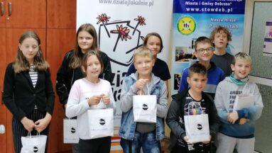 """Grupa dzieci i młodzieży pozuje do zdjęcia pod banerem """"Działaj Lokalnie"""""""