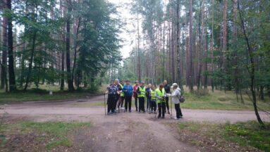 Grupa osób podczas wyprawy z kijami pozuje w lesie do zdjęcia