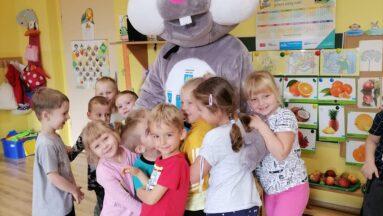 Grupa przedszkolaków przytula Kicaka w nowym futerku