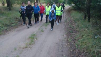 Na zdjęciu grupa osób maszeruje w lesie