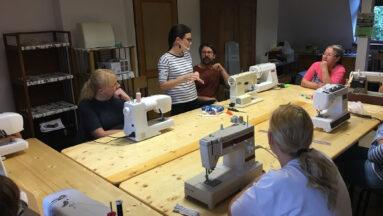 Na zdjęciu widać nauczycielkę przy maszynie oraz grupę osób podczas lekcji szycia