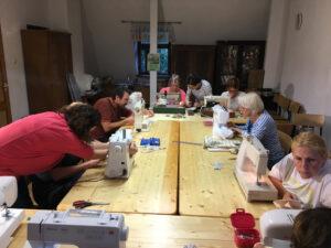 Grupa osób siedzi przydużym stole podczas lekcji szycia