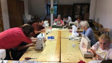 Grupa osób siedzi przy dużym stole podczas lekcji szycia