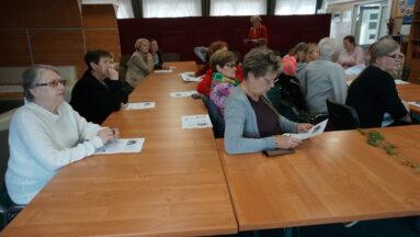 Na zdjęciu widzimy osoby siedzące przy stołach, słuchające wykładu