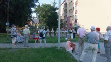 Zespół stojący w odległości od mieszkańców gra koncert